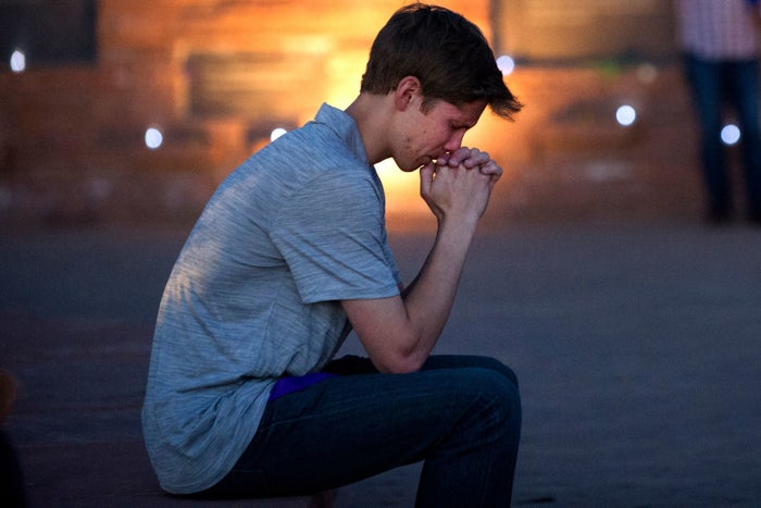 Spencer Greenlee, a senior a Columbine High School, prays at the Columbine Memorial during a vigil Friday at Clement Park in Littleton, Colorado.
