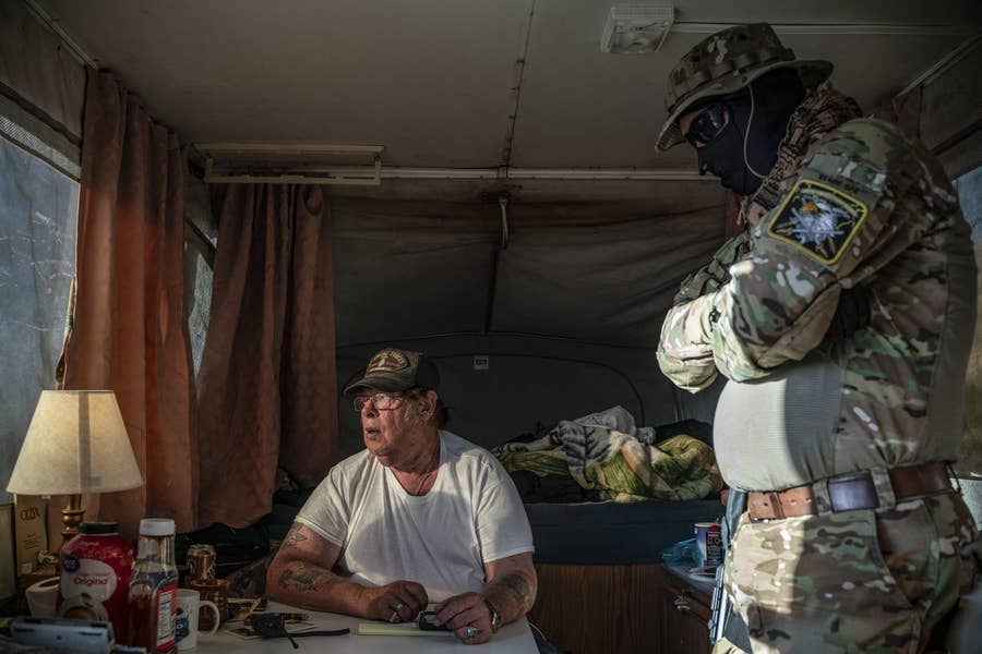 Members of the United Constitutional Patriots speak inside the group's camper in Anapra, New Mexico.