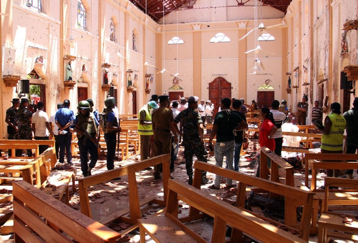 Sri Lankan security personnel walk through debris following an explosion in St. Sebastian's Church in Negombo, north of the capital Colombo, on April 21.