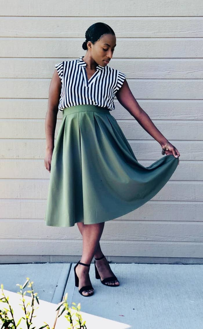 a reviewer wearing the skirt in green with heels and a striped shirt