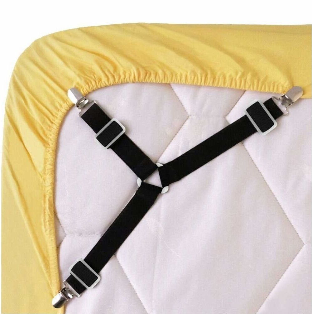 The black clip-on straps, which look like a three-pronged suspender, securing the edges of a fitted sheet around the bottom of a mattress