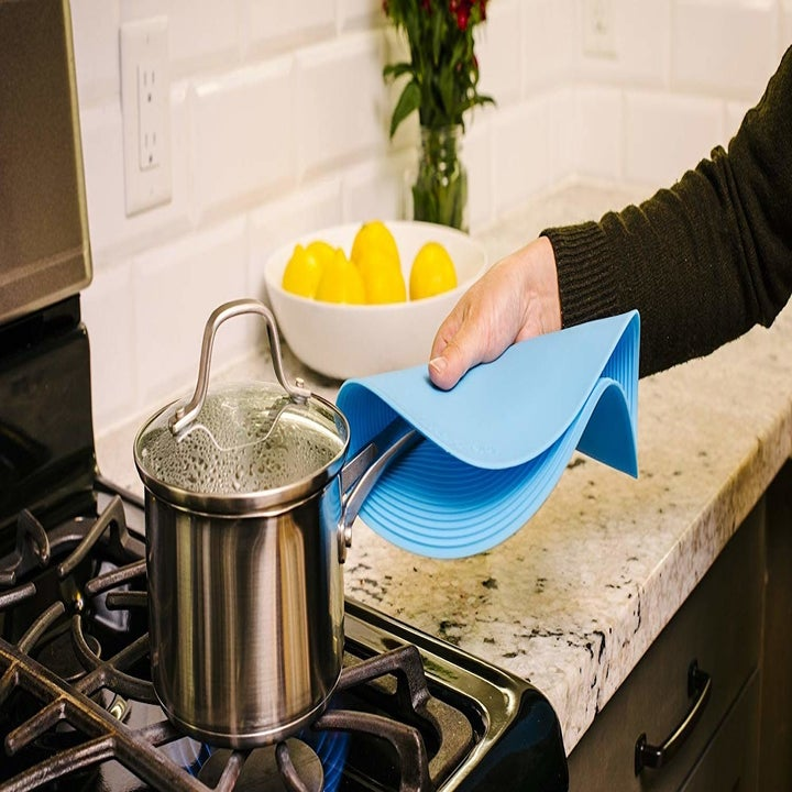 person using the safe grabs to grab a pot handle