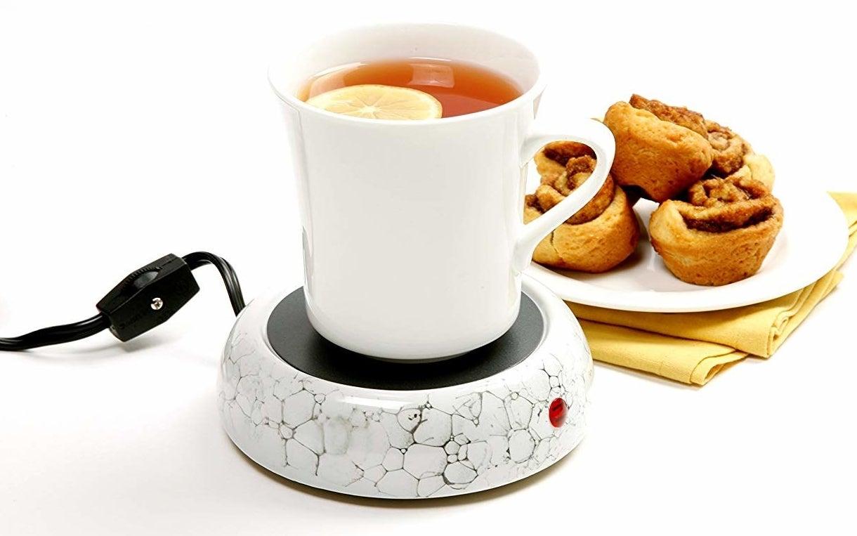 Cup of tea placed on ceramic mug warmer