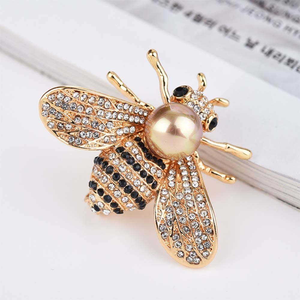 The gold, with black and clear rhinestone bee brooch with a large pearl as part of the body