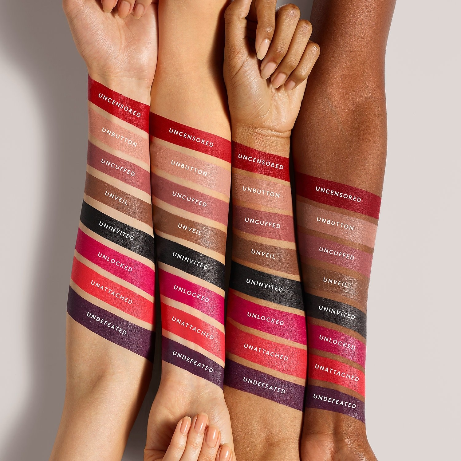 Four arms in different skin tones showing the lipstick colors, including pinks, red, purple, black, and brown