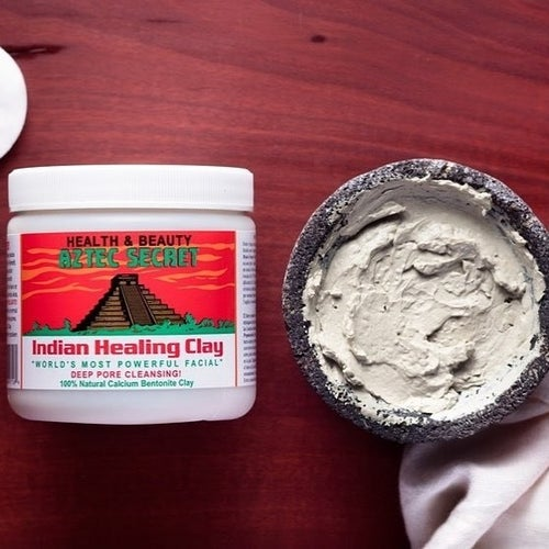 Bottle of bentonite clay powder next to bowl of the mask mixed with liquid