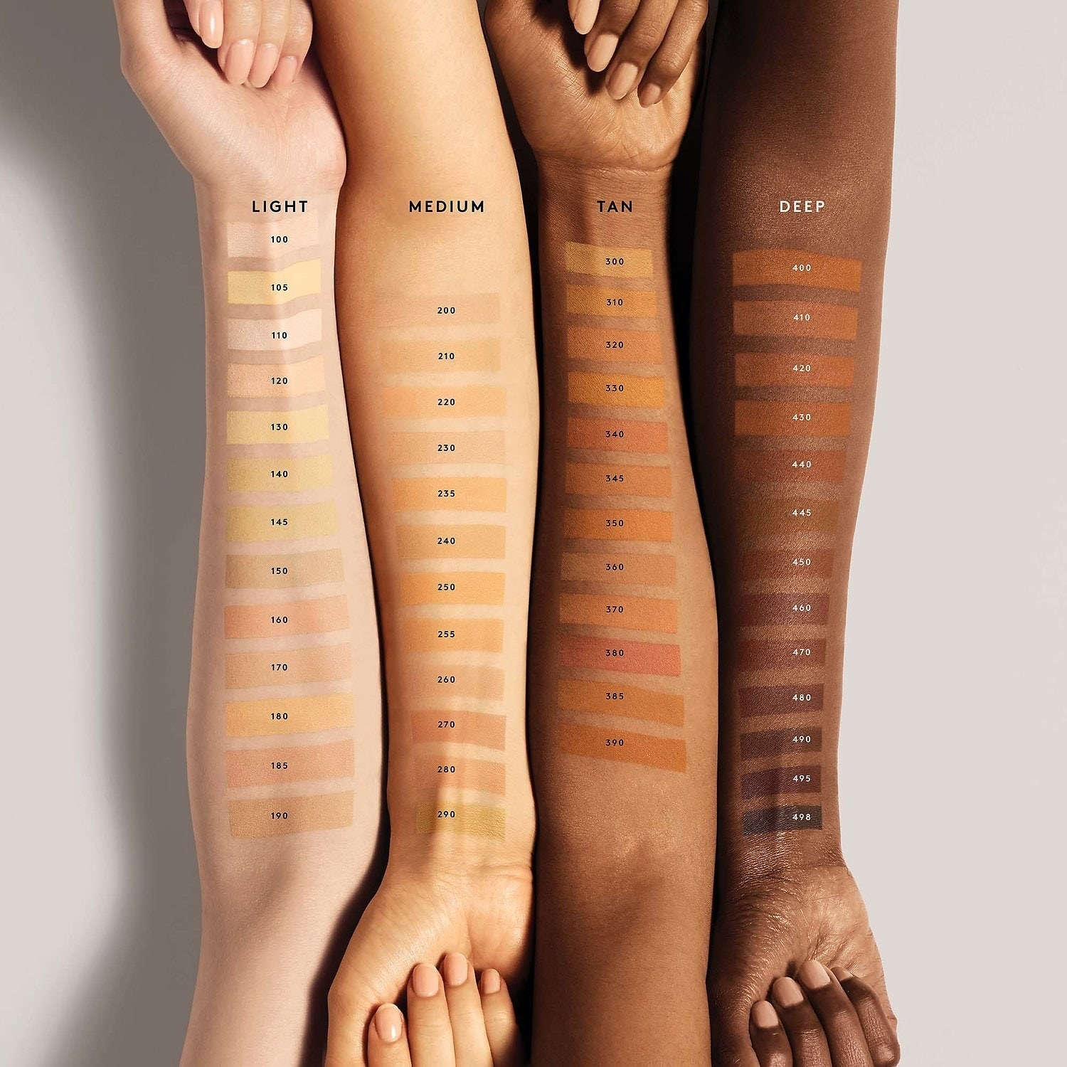 """Four arms with swatches of the foundation in """"light"""" """"medium"""" """"tan"""" and """"deep"""" shades"""