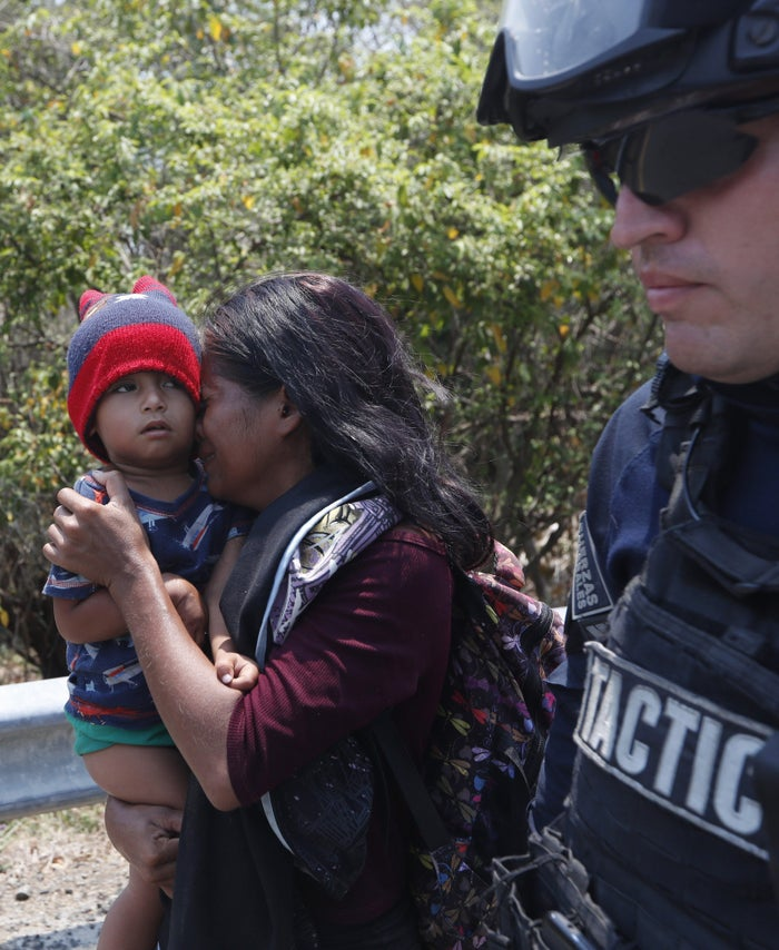 A Central American woman and her son walk with a Mexican Federal Police agent as they are taken into custody.