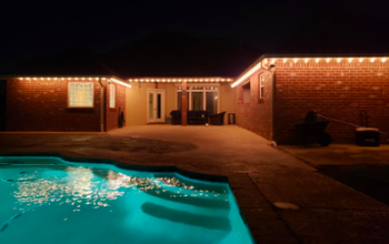 reviewer pic of the string lights along roofline in back of house by a pool patio area