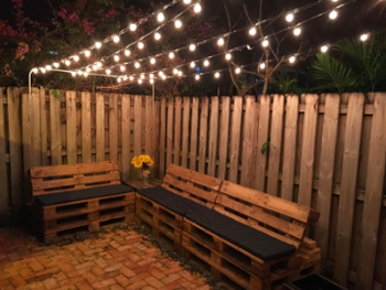 reviewer pic of lights strung up in lines above a patio area with benches