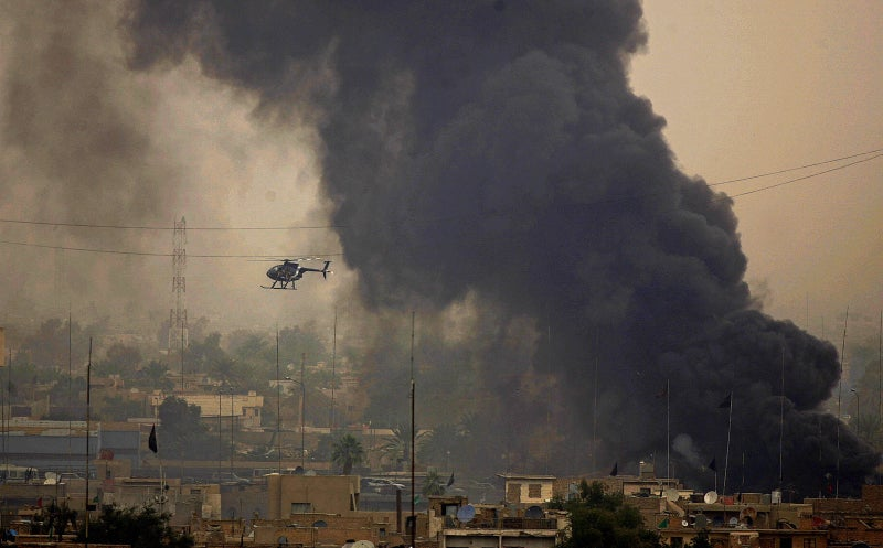 A Blackwater helicopter flies close to black smoke billowing from a fire in an area in central Baghdad on March 3, 2005.