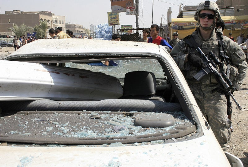A US soldier stands guard at the site of a car-bomb attack in Baghdad on Sept. 17, 2007.