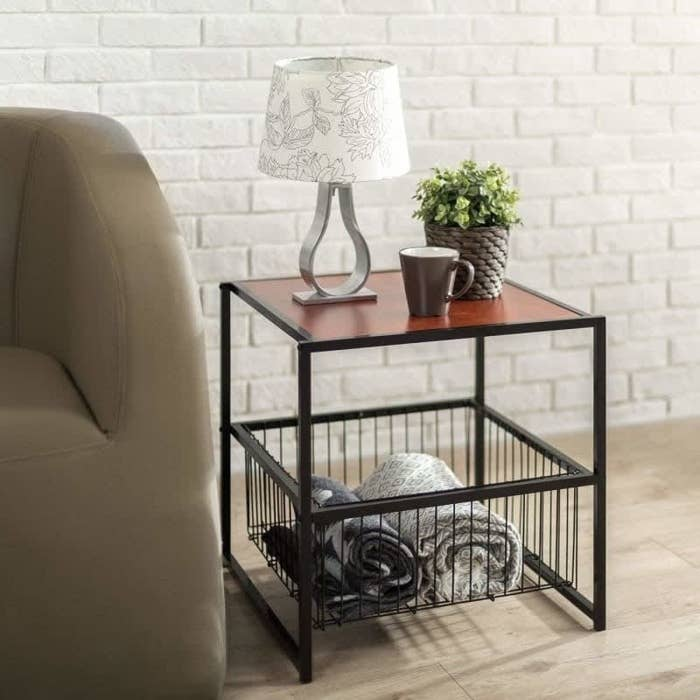 the end table with wood top and black frame and a wire basket on the bottom