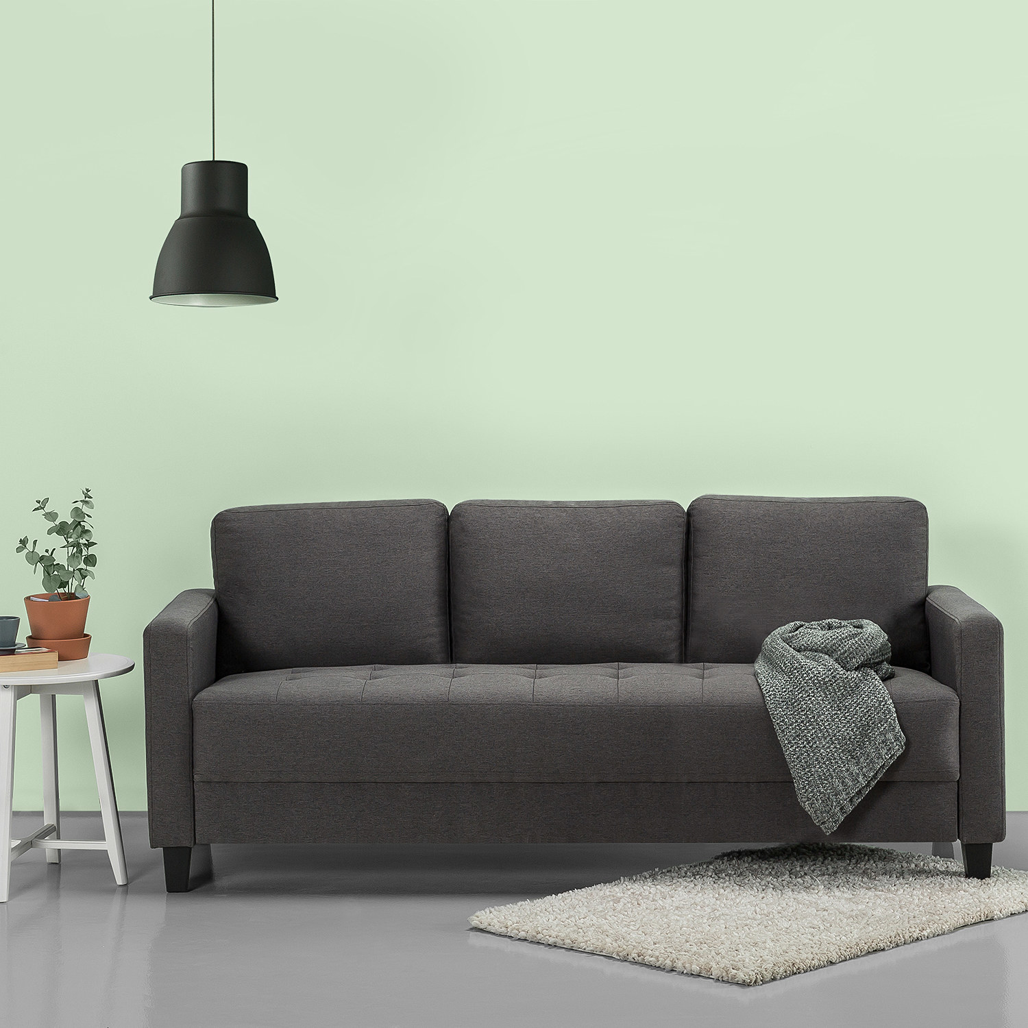 The sofa in dark grey with three seat-back cushions and tufted seat in a room