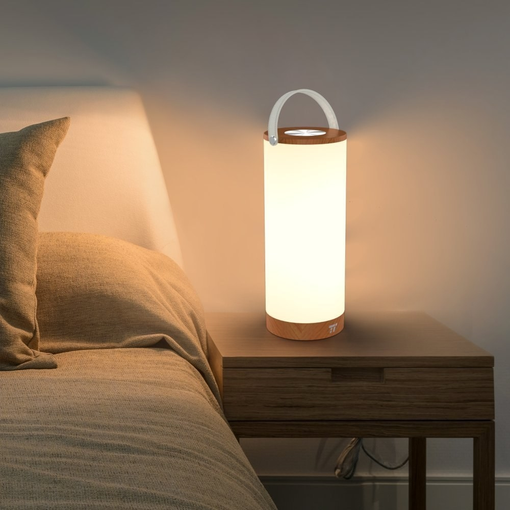 The cylindrical lamp illuminating a bedside table