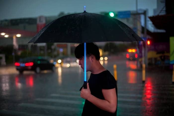 """It's powered by three AAA batteries and has seven LED color options. There's an on/off button as well as a flashlight on the bottom!Promising review: """"This umbrella ROCKS! It was a gift for my husband. It dries quickly so he doesn't have to carry around a dripping umbrella. The 'saber' aspect of it has the option to choose a color or even have them alternate. They all look really vivid and beautiful, especially at night. The flashlight on the bottom is really helpful at night when we're walking our dog, too. My husband gets tons of comments on this umbrella, and I plan to buy more in the future. Really, it's the coolest umbrella ever."""" —TrivialShark388Get it from Amazon for $25.99 (available five colors)."""