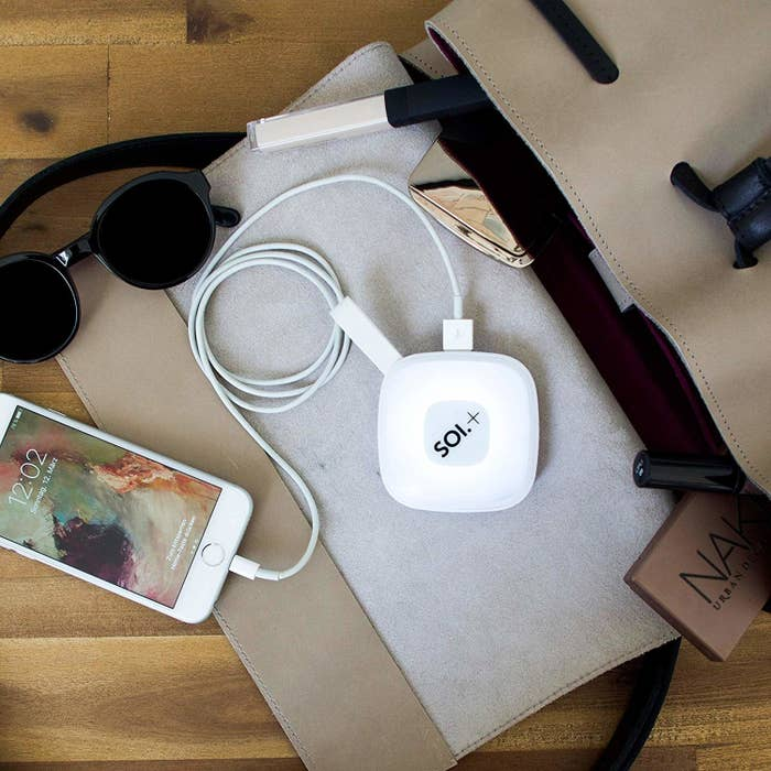 An iPhone plugged into the glowing handbag light via a charging cable. The light is roughly the size of a compact mirror