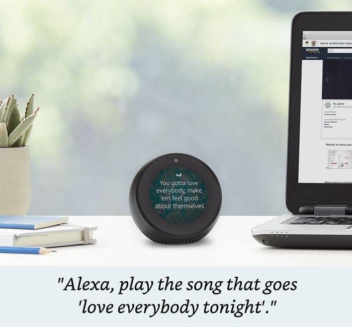 The Echo Spot displaying song lyrics on its round screen. It is roughly the size of a magic 8 ball