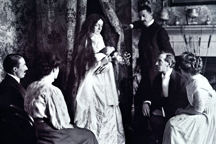 """""""Magician William S. Marriott stands in the background, ostensibly witnessing the emergence of a female apparition carrying a 'spirit' bird and flowers. This was one of many glass lantern slides used by psychic investigator Harry Price in his talks, to demonstrate the methods and equipment regularly used by fraudulent mediums at the time."""""""