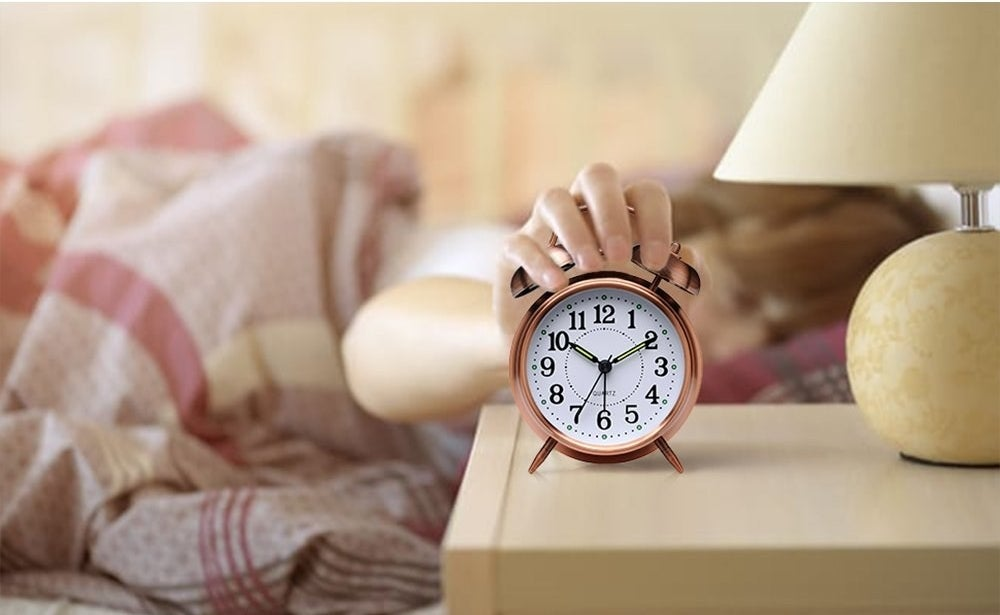 copper color alarm clock on night stand with person in bed reaching over to turn it off