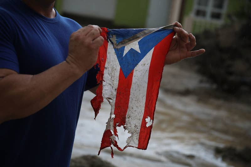 Jose Javier Santana holds a Puerto Rican flag he found on the ground after Hurricane Maria.