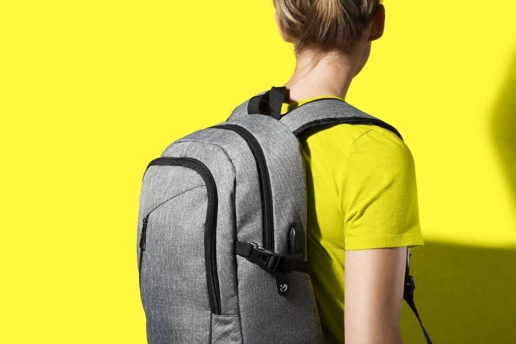 Model wearing the grey backpack with two big zipper pockets and a front small zipper pocket