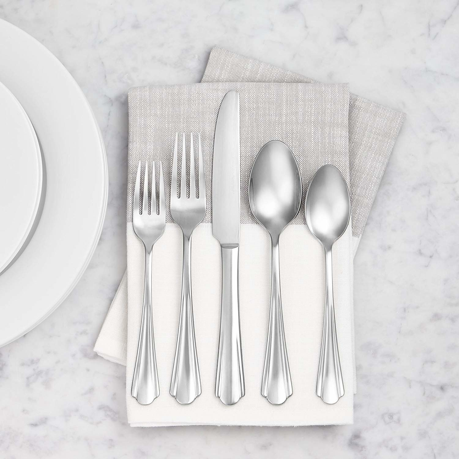 napkin beside of dinner plate on table with all five pieces of silverware in the set