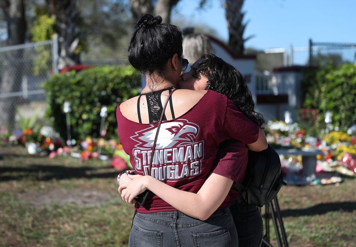 People hug as they visit a memorial set up near the Marjory Stoneman Douglas High School