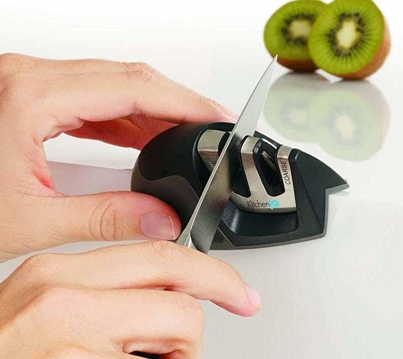 "Two hands using the knife sharpener. It balances on the edge of the counter and has a plastic grip to hold, and two sharpening slots (one labeled ""coarse"", one labeled ""fine)"