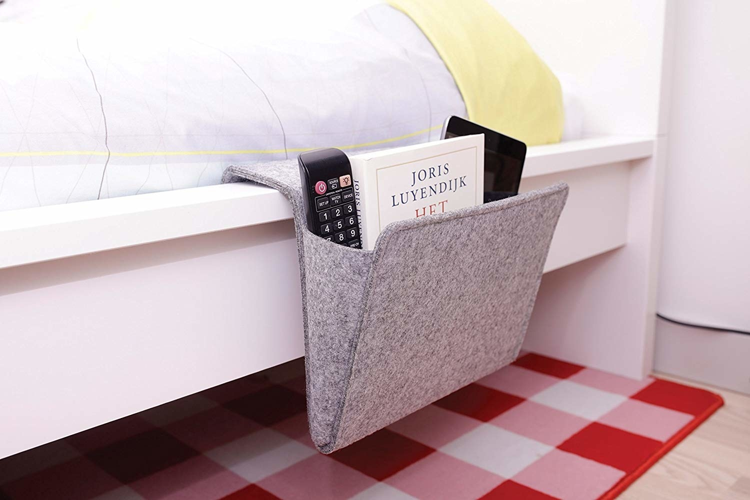 pouch caddy hanging off side of bed with stuff like a book and remote in it