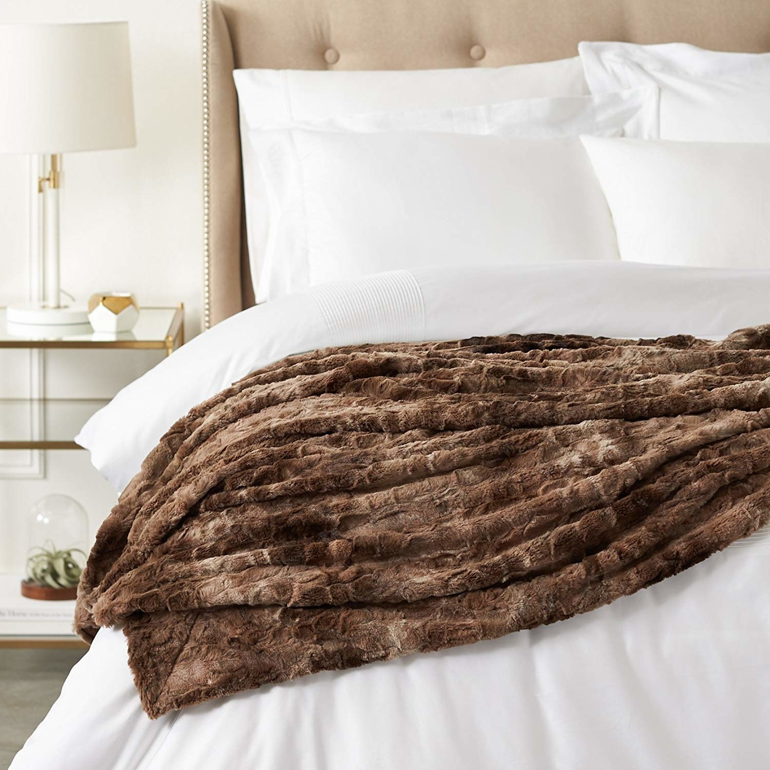 brown faux fur blanket thrown on top of made bed