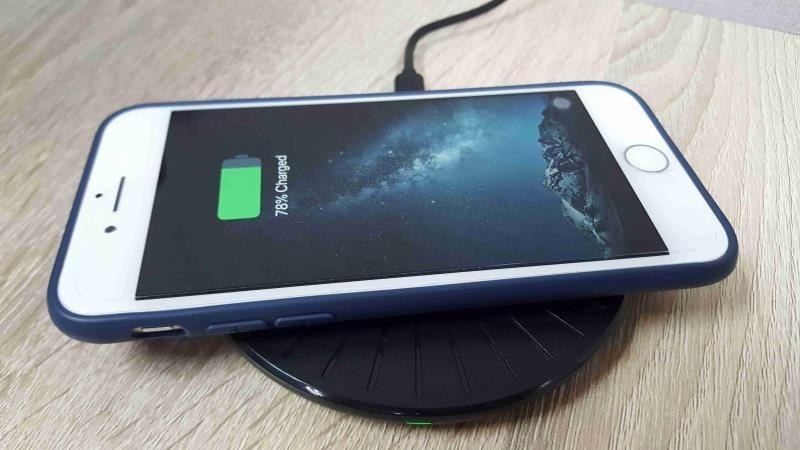 An iPhone, placed on top of the Qi charger, which looks like a small round plate