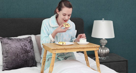 person using the table-like wood lap desk in bed to hold a breakfast plate, cup of coffee