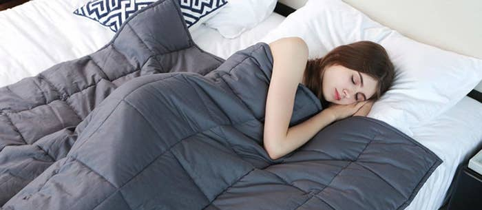 person under the weighted blanket asleep in bed