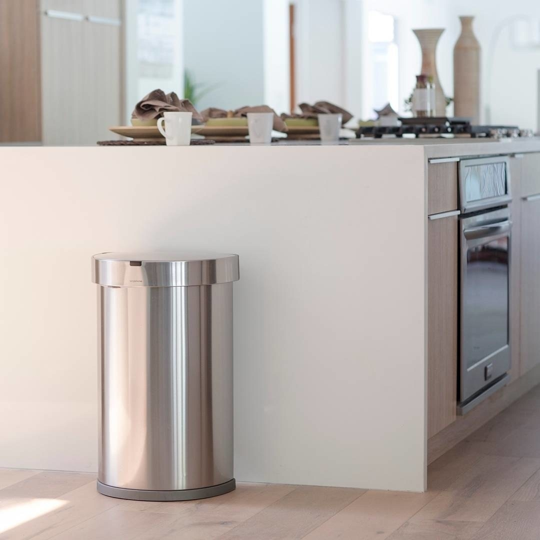 The stainless steel trash can placed next to a kitchen counter