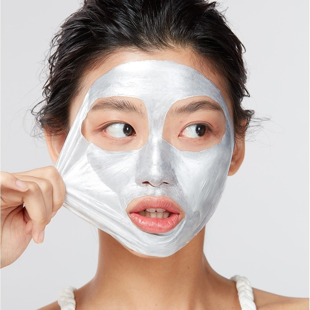 A person peeling the silver-colored mask off their face in one piece