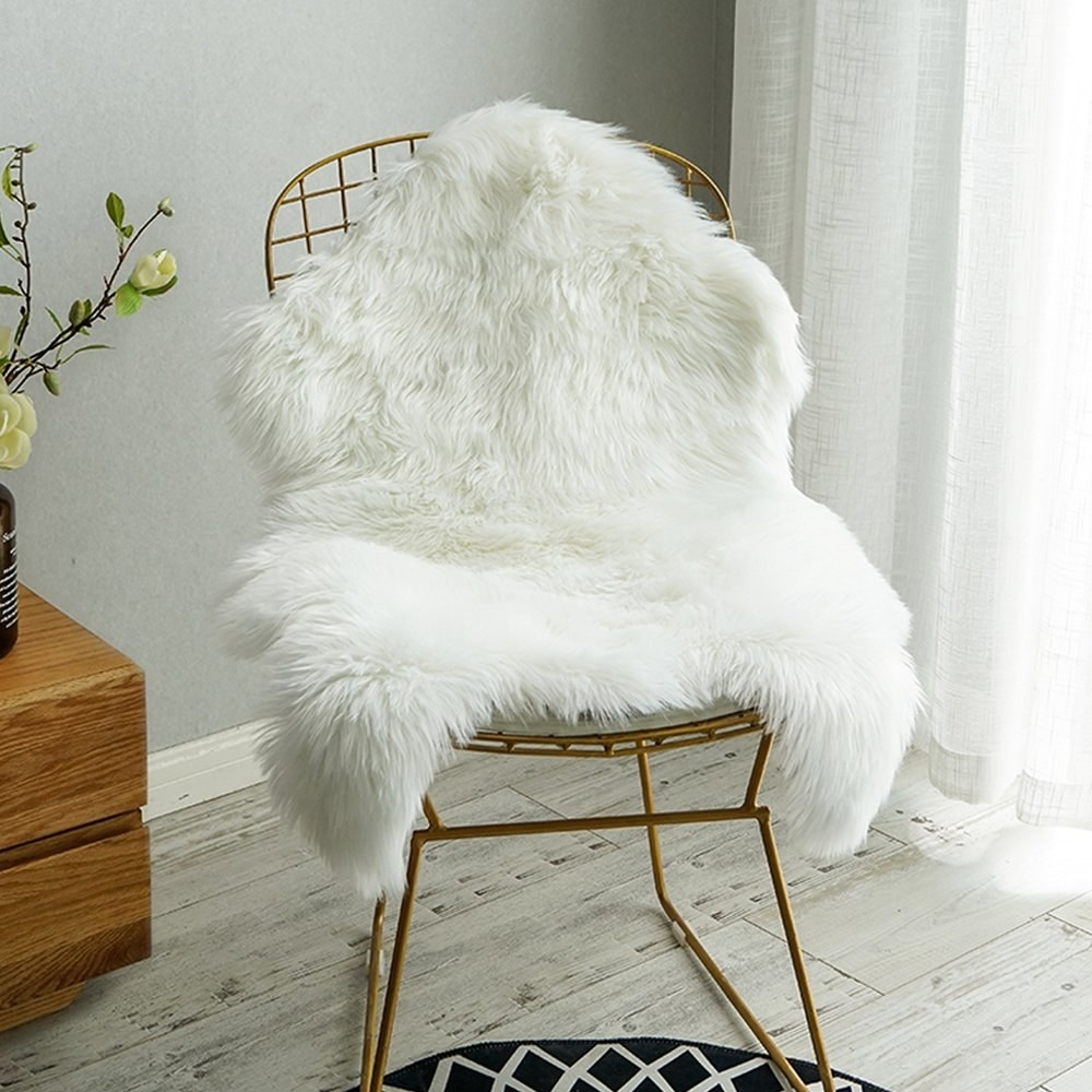 white faux fur sheepskin-like rug on a wire chair
