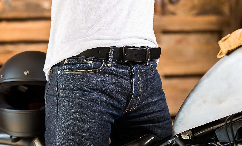 The plain black buckle belt on a model, who's wearing jeans