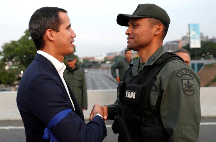 Juan Guaidó shakes hands with a member of the military supporting him on Tuesday.