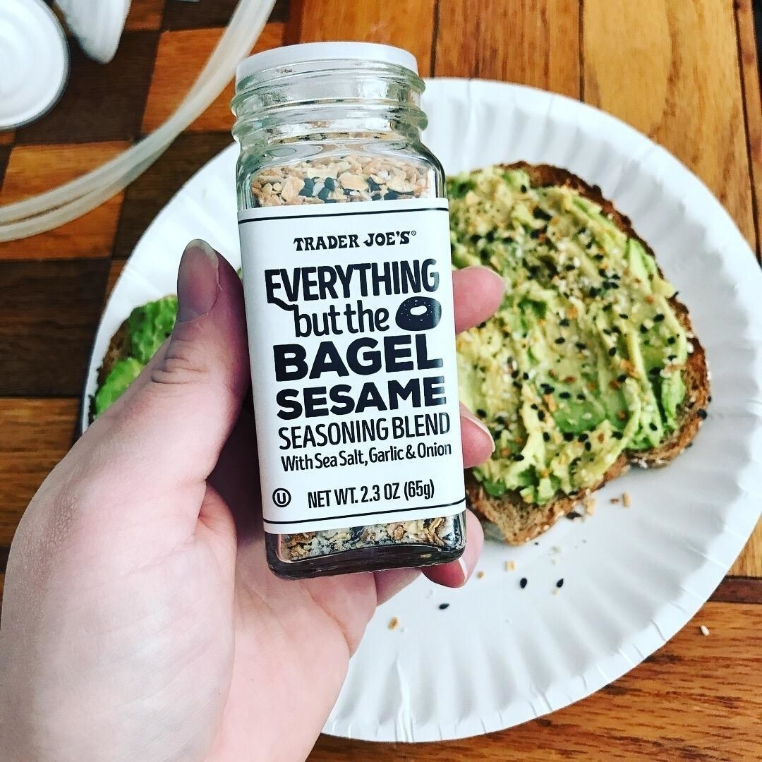 "A hand holding the 2.3 ounce (65 gram) bottle of seasoning over some avocado toast with the seasoning sprinkled on it. The bottle has the name of the blend on it and says ""with sea salt, garlic, and onion"""