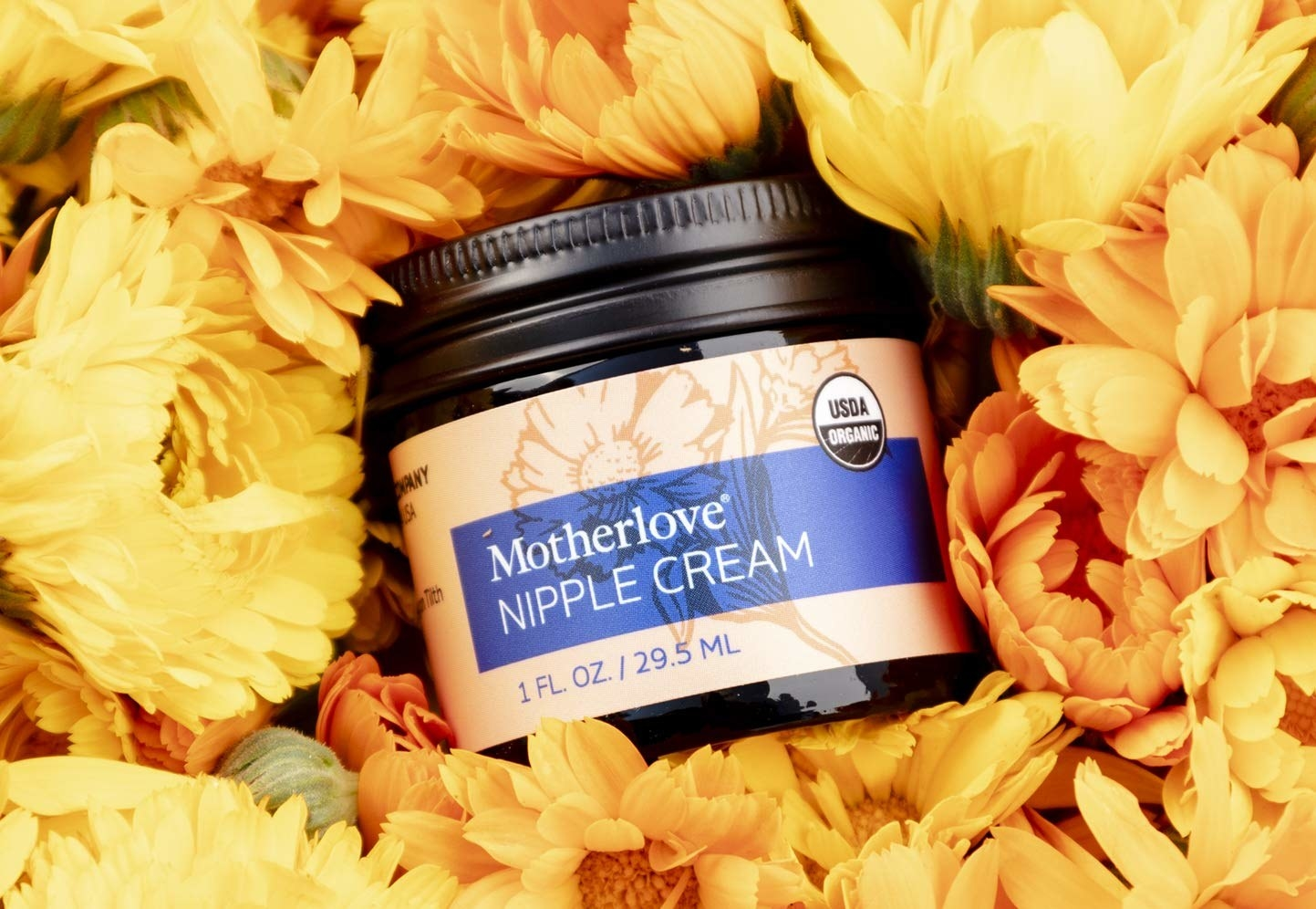 jar of Motherlove nipple cream surrounded by yellow flowers