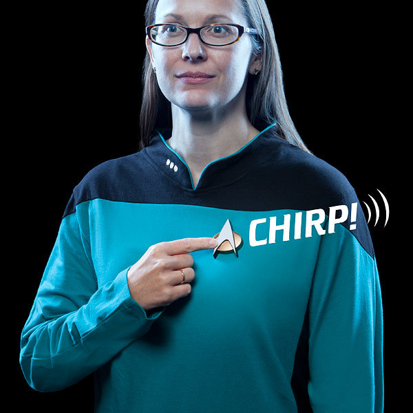 A person dressed in a Starfleet uniform pressing the Bluetooth ComBadge which appears to produce a chirping sound