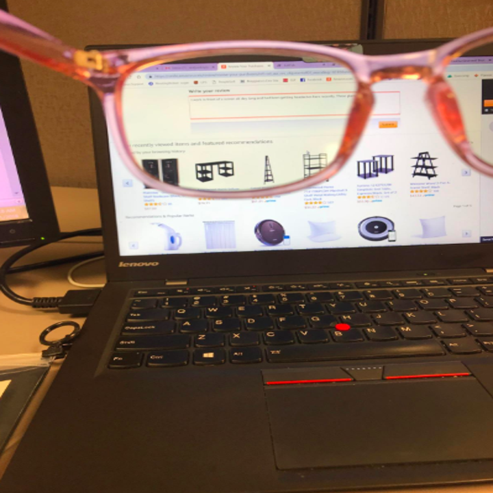Reviewer photo of blue light glasses being held up in front of a computer screen