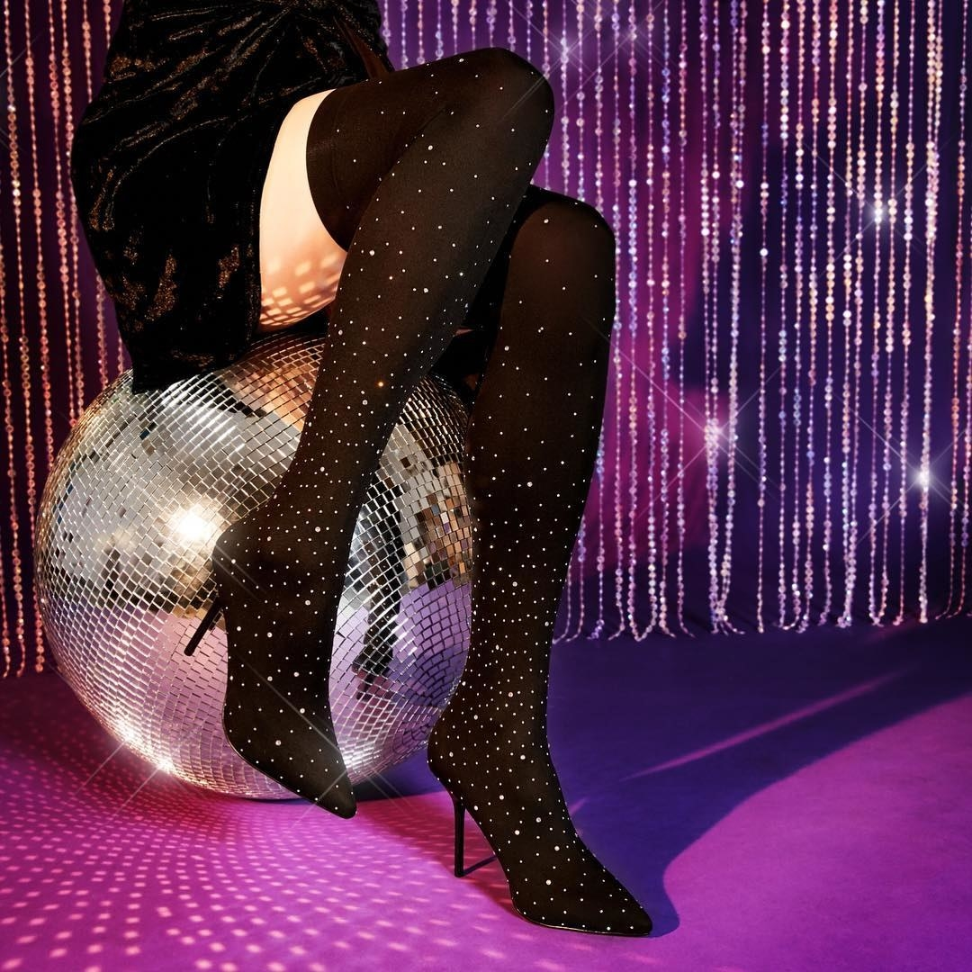 The thigh-high sock boots with thin stiletto heels, a black fabric, and sparkling crystal details throughout