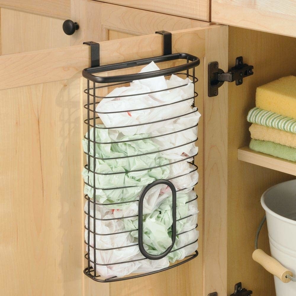 The organizer hanging inside a cabinet and filled with plastic bags. There's a hole for easily pulling out one bag