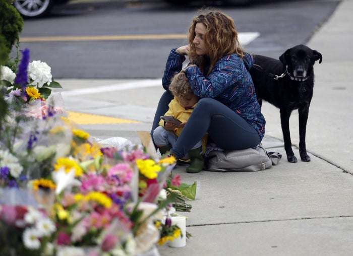 A woman pauses at a growing memorial across the street from the Chabad of Poway synagogue, April 29.