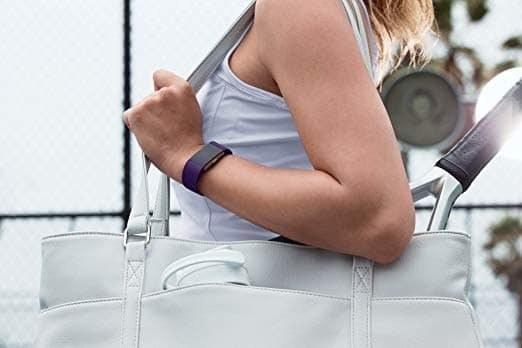 Model wearing the Fitbit that looks like a bracelet on their wrist in purple