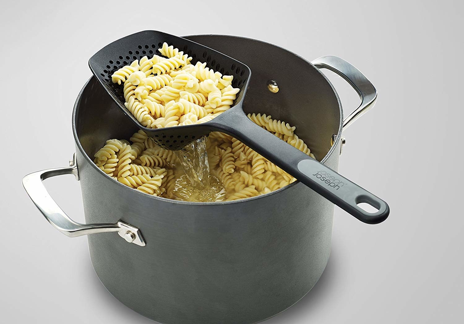 The scoop with draining fusilli in it, resting on top of a pot of pasta and water,