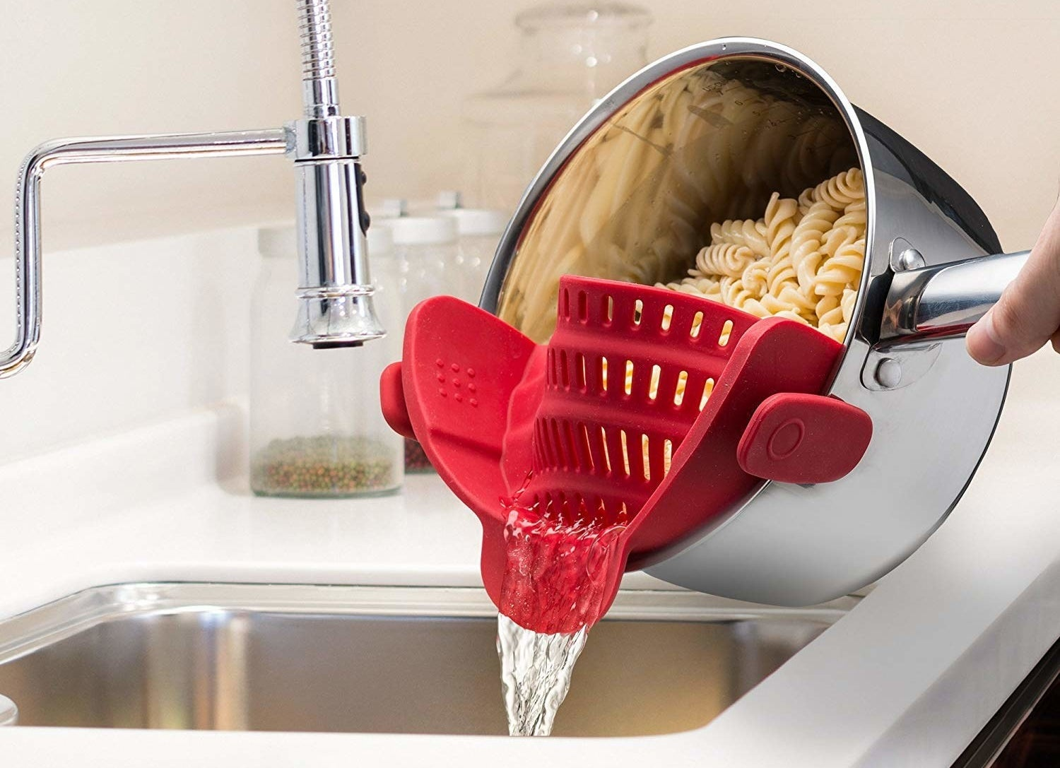 One hand pouring water out of a pot of pasta using the red strainer
