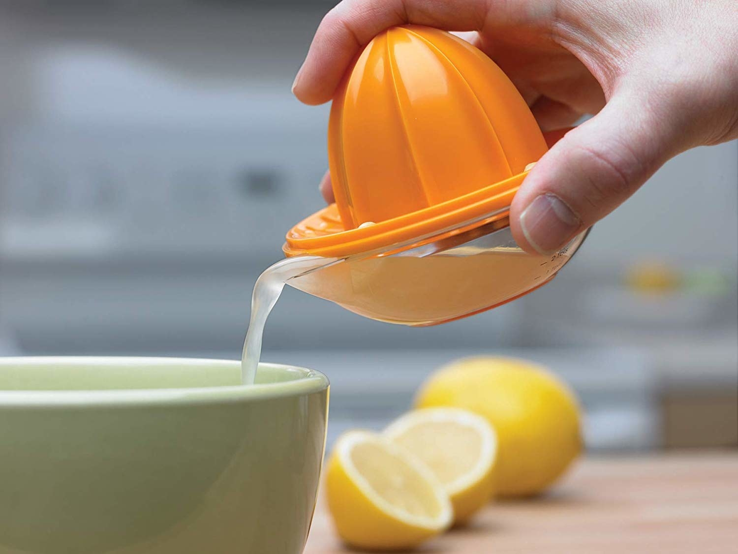 Hand pouring juice from the juicer into a bowl